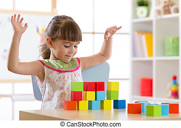 Little girl build block toys at home or daycare. Kid playing with color cubes. Educational toys for preschool and kindergarten children.