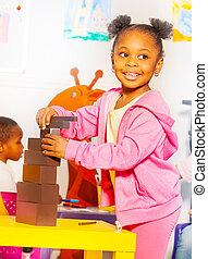 Little girl building blocks in nursery school