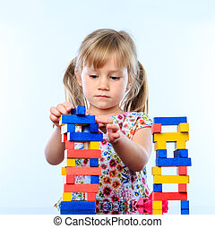 Little girl building structure with wooden blocks.