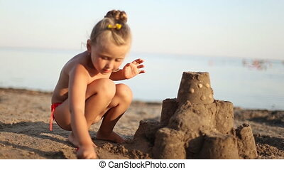 little girl builds a sand castle