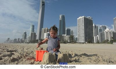 Little girl builds sand castle in Surfers Paradise Australia...