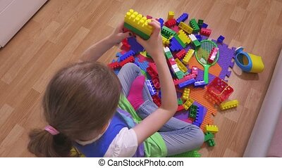 Little girl built tower from toy bricks