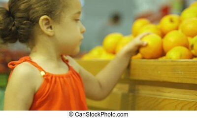 Little girl buys peaches. The little girl herself chooses food. 4k.