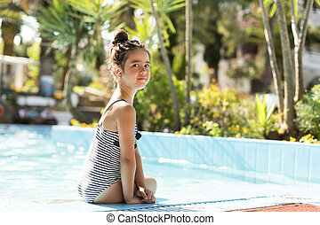 Little girl by the swimming pool