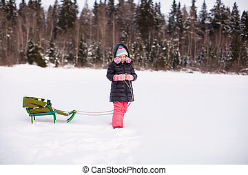 Little girl carries her sled ride in the snow