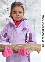 Little girl carrying a log through the snow