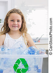 Little girl carrying box full of empty plastic bottles