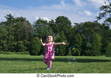 Little Girl Catching Bubbles - Little Girl in Pink Outfit...