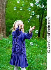 Little girl catching bubbles