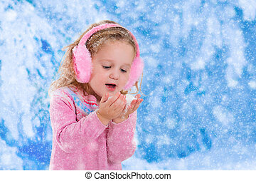 Little girl catching snow flakes - Little girl in pink ...