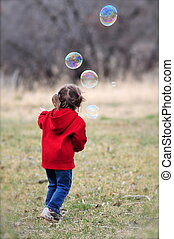 Little Girl Chases Big Bubbles