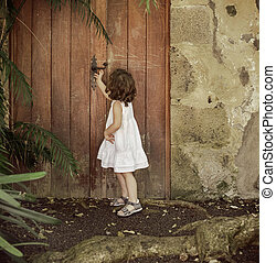 Little girl checking old, wooden door