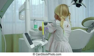 Little girl checks dental equipment in cabinet - Fair haired...