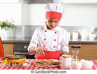 Little girl chef sprinkle with sugar baked waffles