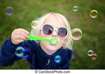 Little Girl Child Blowing Bubbles Outside on a Summer Day