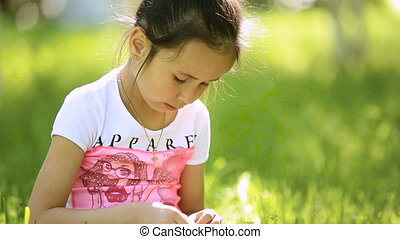 Little girl child brunette latina sits in the grass, knits a...