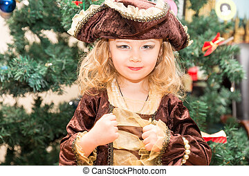 Little girl child dressed as pirate for Halloween  on background of Christmas tree. Kid in carnival costumes for Christmas