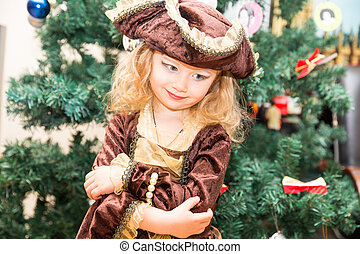 Little girl child dressed as pirate for Halloween  on background of Christmas tree