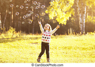 Little girl child enjoying playing with soap bubbles in autumn park