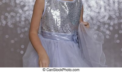 little girl child in a silver dress dancing on background of silver bokeh.