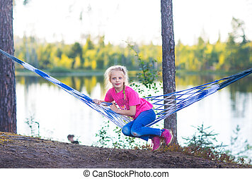 Little girl child in hammock near the lake