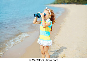 Little girl child looks in binoculars on beach near sea