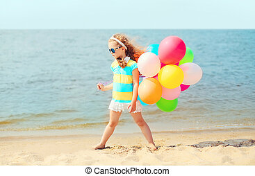 Little girl child on summer beach playing with colorful balloons near sea