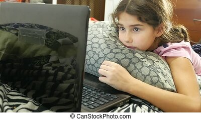 little girl child playing in the notebook online game laptop...