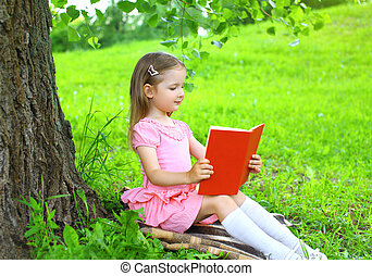 Little girl child reading a book on the grass near tree in summer day