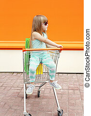 Little girl child sitting in shopping cart with bags outdoors