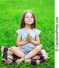 Little girl child sitting on the grass does yoga exercise outdoors