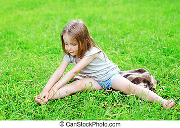 Little girl child sitting on the grass does yoga stretching exercise outdoors