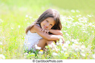 Little girl child sitting on the grass in sunny spring meadow