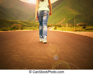 Little girl child walking on road to mountains at sunset