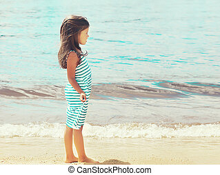 Little girl child walks on the beach near sea in profile
