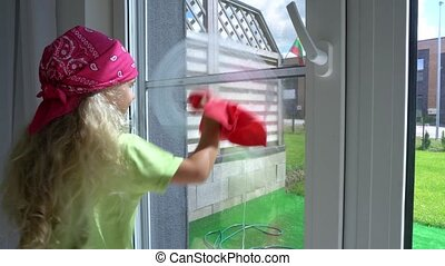 Little girl child washes window at home. Gimbal motion shot