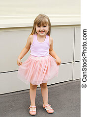 Little girl child wearing a pink skirt outdoors having fun