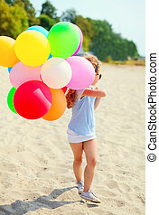 Little girl child with colorful balloons walking on beach