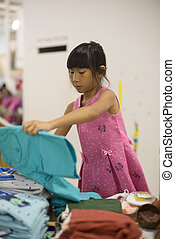 Little girl chooses an outfit of a blouse and skirt in store of children clothing