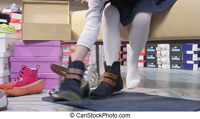 Little girl choosing and trying on new shoes in childrens shoe store