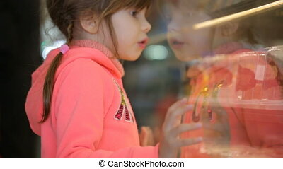 Little girl choosing cake at grocery store