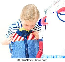 Little girl choosing dress in clothing store.