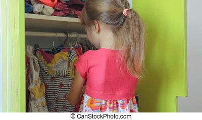 Little girl choosing dress in her wardrobe
