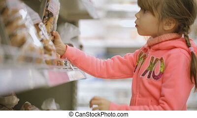 Little girl choosing foodstuff at grocery store