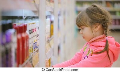 Little girl choosing goods at shop