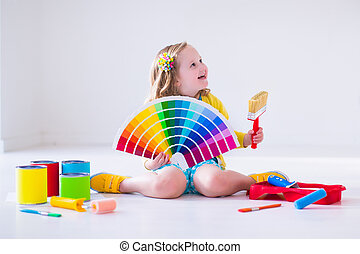 Little girl choosing paint color for wall - Family...