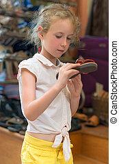 Little girl choosing sandals in the market.