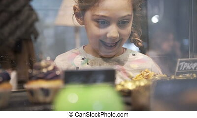 Little girl chosen Cake and desserts. Window of cake shop with variety of cakes on display