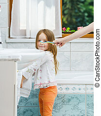 Little girl cleaning the teeth