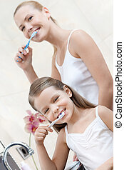 Little girl cleans teeth with her mom